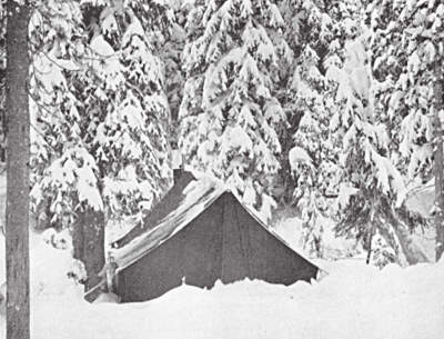 wall tent and stove in a snowed-in hunting camp